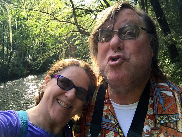 Mark makes a funny pursed up lip face in front of a dappled green river under the trees. Laurie leans on his shoulder.