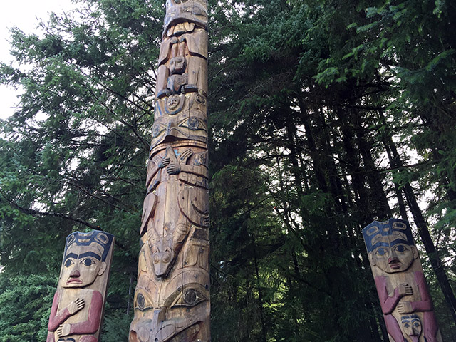 3 large totem poles against a background of large fir trees.