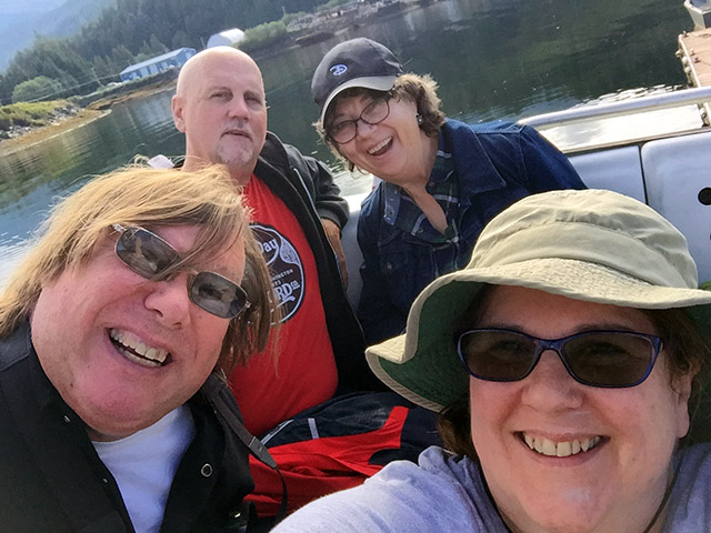 Laurie and Mark with Laurie's cousin and his wife cram into the selfie with clear water behind.