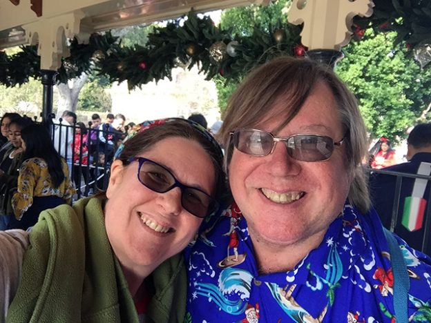 Laurie and Mark waiting for the train at Disneyland during the holiday season. Mark is wearing his Hawaiian surfing Santa shirt.