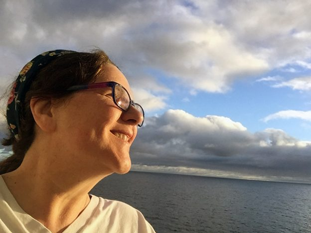 Laurie smiling in profile against a cloudy sky at sea with blue skies peeking through.