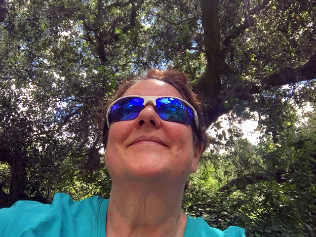 Laurie under a tree looking up wearing shiny navy lenses in stark white sunglass frames.