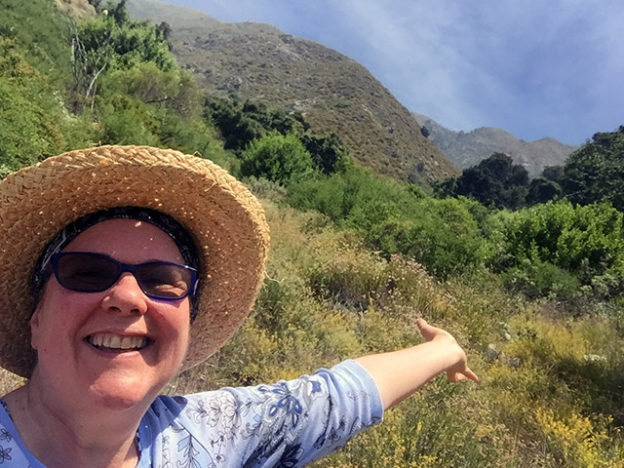 Laurie smiling in a broad staw hat with arms outflung in the meadow at the top of the mountain and foothills in the background.