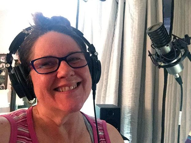 Laurie smiles in her studio wearing headphones in front of her mic