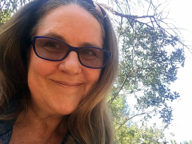 Laurie with her hair down smiling under a tree
