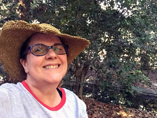 Laurie smiles under a floppy straw hat in the woodland
